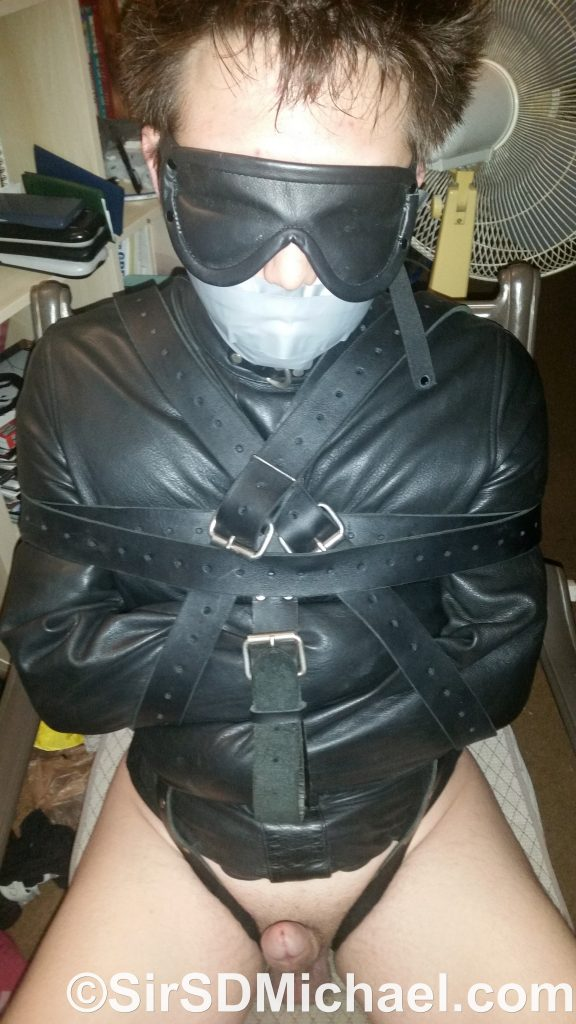 Boy strapped tightly into a straitjacket. A happy boy at that.